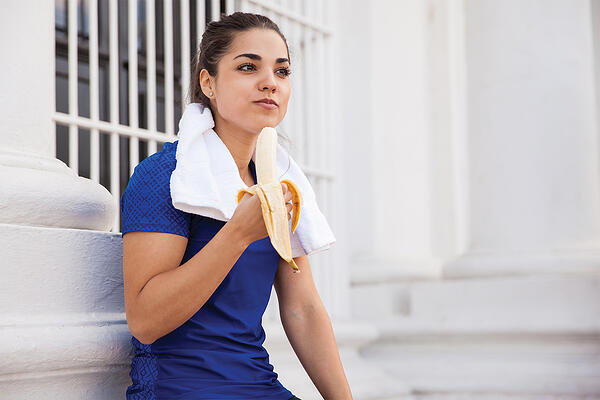 trainer eating a post-workout banana